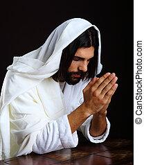 Praying Jesus Christ of Nazareth kneeling hands together