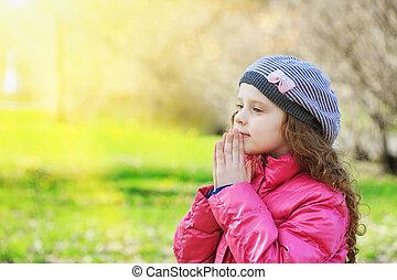Praying little girl in spring park.