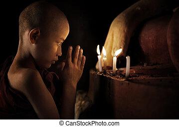 Praying - Little novice monk praying in front candlelight