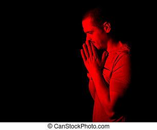 Praying man in red light standing in studio