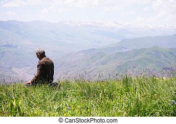 Senior man kneeling while praying in mountains rear view