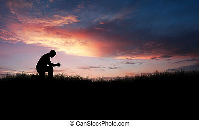 Praying Man - Man kneeling down in a field to pray