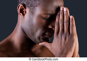 Praying man. Side view of young African man praying while holding hands clasped near and against grey background