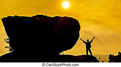 Praying man silhouette on sunset background with big stone