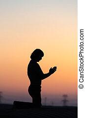 Praying man silhouette sitting alone in desert at sunset