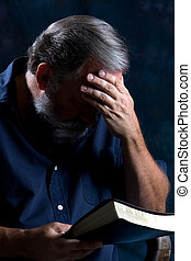 Praying Man - Man holds his head in one hand and bows to...