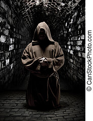 Praying monk in dark temple corridor - Mystery monk praying...