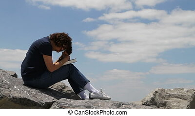 Mature woman holds a bible in her lap with head bowed praying sitting on large rocks with a cloudy blue sky background.
