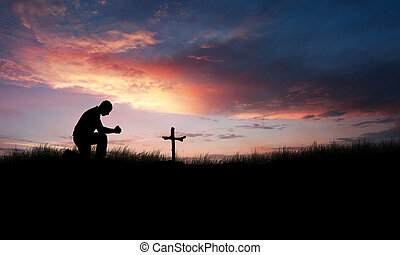 Man praying over a cross and grave