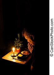 Praying over TV Dinner - A middle-aged man praying over a TV...