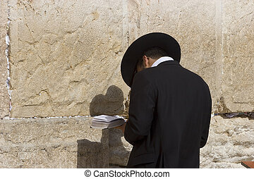 Praying - The orthodox Jew reads a pray at a western wall