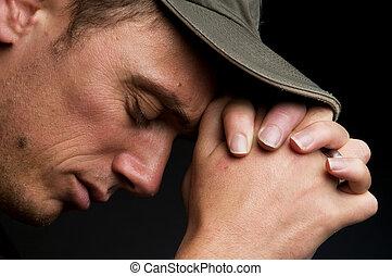Praying - Young man praying, on a black background.
