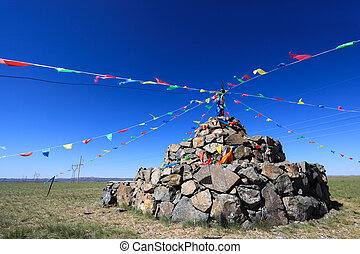 praying stone and prayer flags on steppe in inner mongolia