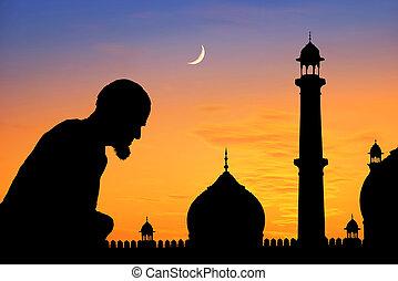Praying time - Silhouette of an old muslim praying at...