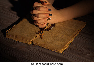 Praying to God, folded Christian woman hands with holy bible and rosary.
