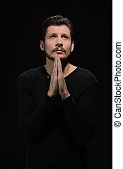 Praying to god. Portrait of bearded man praying and holding his hands clasped