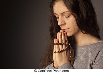 Praying woman on dark background