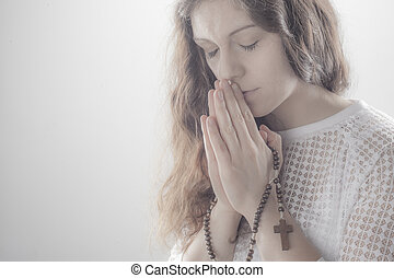 Praying woman on white background with shine.