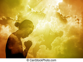 Silhouette of young woman praying at sunset