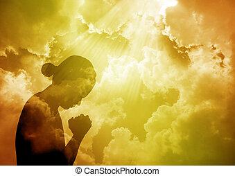 Praying woman - Silhouette of young woman praying at sunset