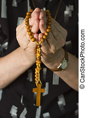 Praying woman - Woman is praying and holding Rosary in both...