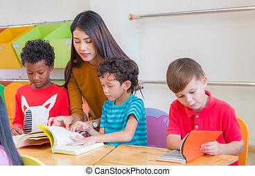 pre escuela, niños, diversidad, concept., libro, hembra asiática, enseñanza, lectura, profesor, aula