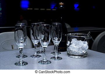 Pre-serving, consisting of a bottle of champagne, glasses and an ice bucket. Background