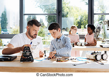 Pre-teen boy and his teacher connecting wires of robot