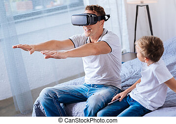 Pre-teen boy watching his father play with VR headset