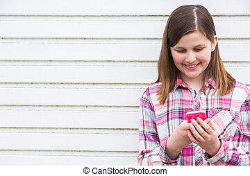 Pre Teen Girl Texting On Mobile Phone In Urban Setting