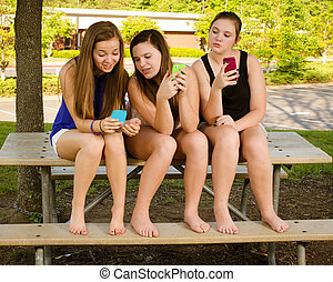 Pre-teen girls texting while hanging out in front of their school