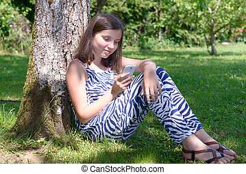 Pre teenager girl texting on mobile phone