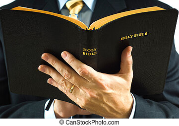 Preacher with Bible - A man is business suit reading the...