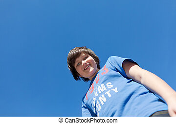 Preadolescence Boy Standing Against Blue Sky