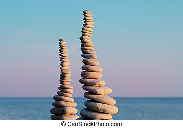 Two pile of pebbles in the balance on the seacoast
