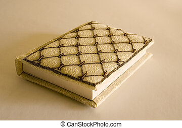 A quilted front book with intricate design on it. plain background.