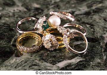 Precious jewels, rings with diamonds, emeralds and corals on green marble