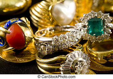 Precious jewels, rings with diamonds, emeralds and corals on pounds in gold