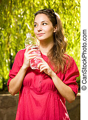 Precious sweet water, portrait of a beautiful young brunette woman with bottled water.