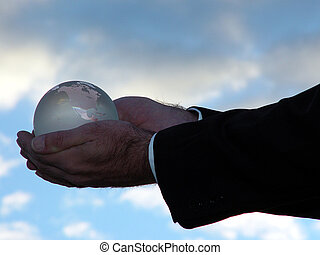 Man holding world globe with his his hand toward the sky.