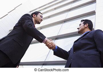 predios, escritório, dois, exterior, homens negócios, mãos sacudindo