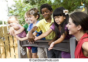 preescolar, niños jugar, en, patio de recreo, con, profesor