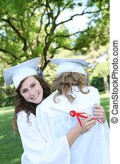 Preety Woman at Graduation - A pretty teenage woman hugging...