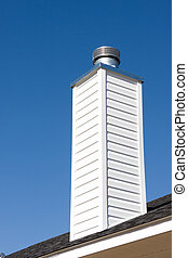 Prefabricated chimney on a recently constructed home rooftop.