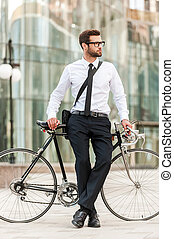 Preferred mode of transport. Full length of handsome young businessman leaning at his bicycle and looking away while standing outdoors