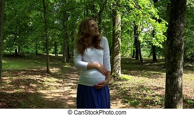 Pregnancy and leisure concept. Pregnant woman in park on...