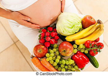 Pregnancy and nutrition - pregnant woman with a bowl of fruit and vegetables on her lap