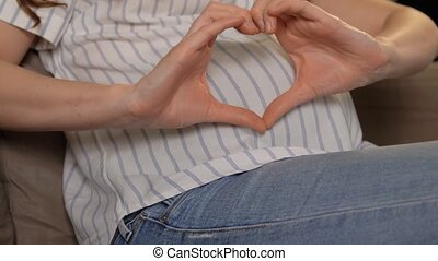 pregnant woman showing hand heart gesture - pregnancy and ...