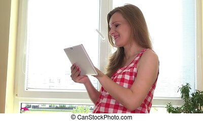 pregnant woman with tablet pc computer preparing vegetable salad at home