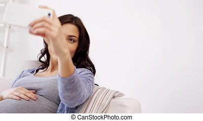 pregnant woman taking selfy by smartphone at home -...